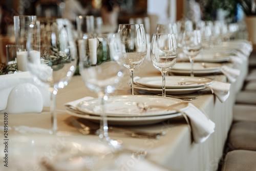 Festive table setting. Glasses, plates, cutlery, napkins. Defocus Fototapete