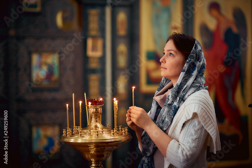 Fototapeta Orthodox woman praying in front of icons in the Church