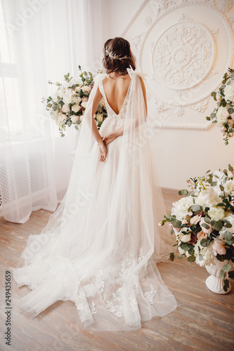 Photo from back Beautiful young woman in white wedding dress smiling Fototapeta