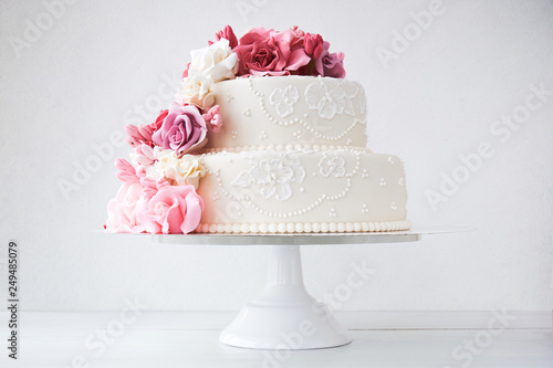 Fotografiet Two-tiered white wedding cake decorated with pink flowers on a white wooden background
