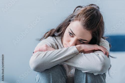 Murais de parede selective focus of beautiful sad woman hugging knees and looking away