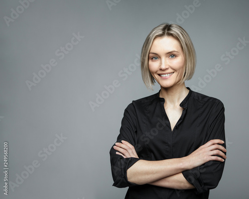 Slika na platnu Beautiful middle-aged woman on a gray background in a black blouse smiling