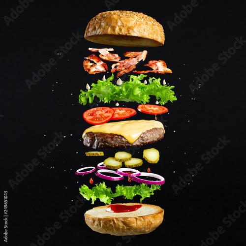 Fotografia Floating burger isolated on black wooden background