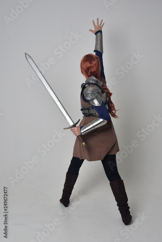Fototapeta full length portrait of a  red haired girl wearing medieval warrior costume and steel armour, standing pose facing away from the camera on grey studio background