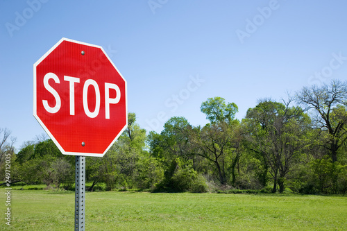 Stop Sign With Green Field And Trees