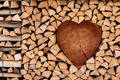Fototapeta Firewood, nicely assembled in the shape of heart, romantic background, wooden te
