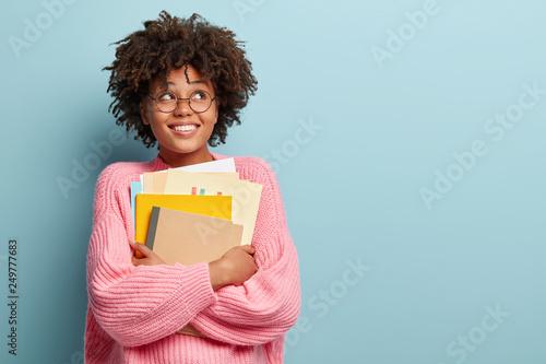 Foto Photo of cheerful pleased schoolgirl looks upwards, dreams about recieving degre