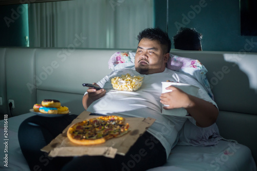 Wallpaper Mural Asian obese man eating junk foods before sleep