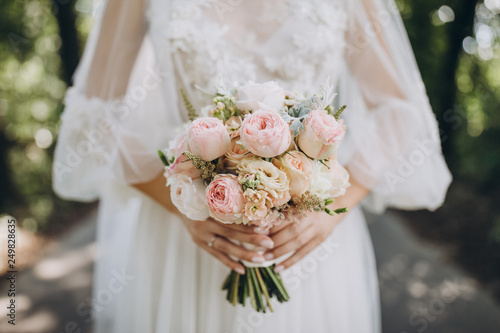 Fotografia bride in a white wedding dress holding a bouquet of roses, peonies and greenery