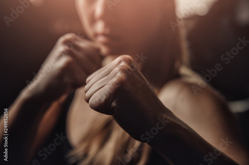 Fotografiet Young female boxer preparing to punch bag