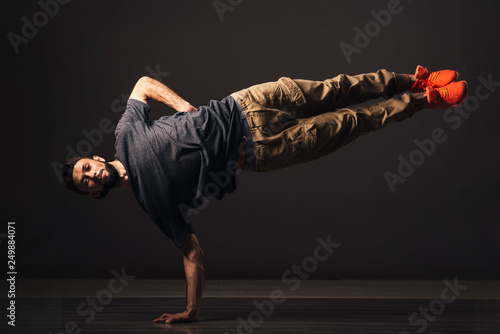 Canvas Print A man hip hop dancer or bboy freezes in one pose on the hand