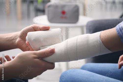 Tablou Canvas Woman applying bandage onto female arm, closeup