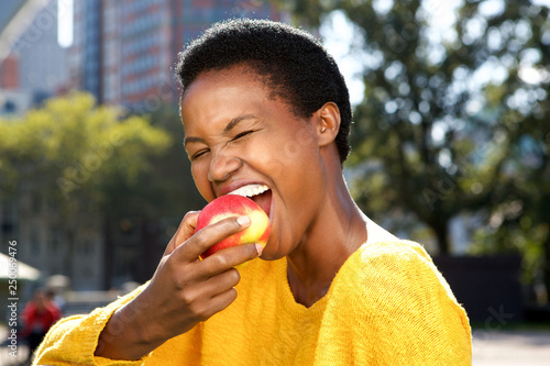 Wallpaper Mural Close up healthy young black woman eating apple outdoors