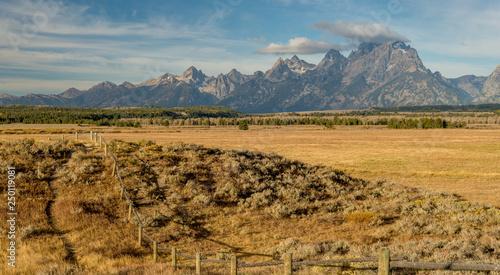 Fotografia, Obraz In Wyoming the Teton mountain range with a rood fences on a farmers field