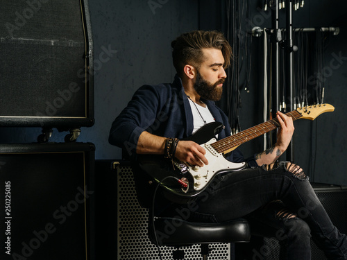 Obraz na plátně Bearded man playing guitar in a music studio