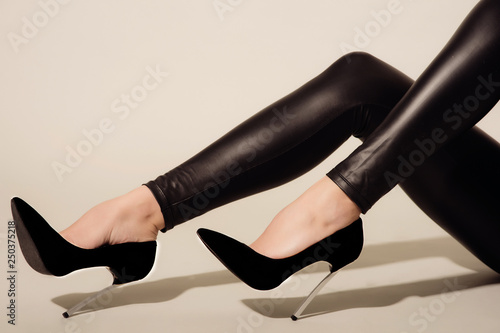 Obraz na płótnie Women's legs in black tight-fitting leather trousers and high-heeled shoes sits