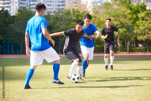 asian soccer players playing on field Fototapeta
