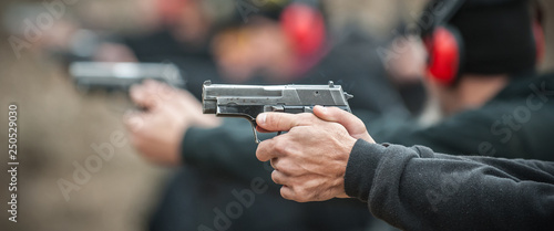 Canvas Print Close-up view of shooter practice handgun shooting in row group