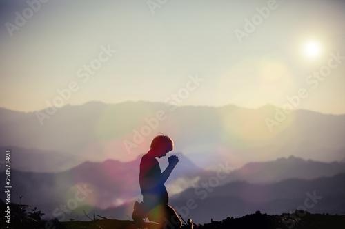 Fotografia Faith of christian concept: Spiritual prayer hands over sun shine with blurred b