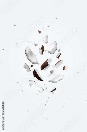 Obraz na płótnie Flying pieces of coconut on white color