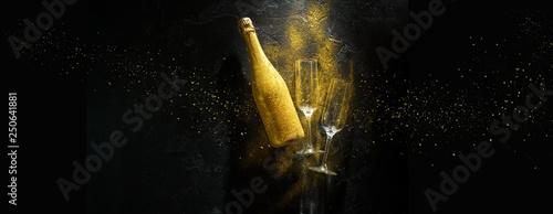 Photo Romantic image of golden champagne bottle, two wine glasses on black stone backg
