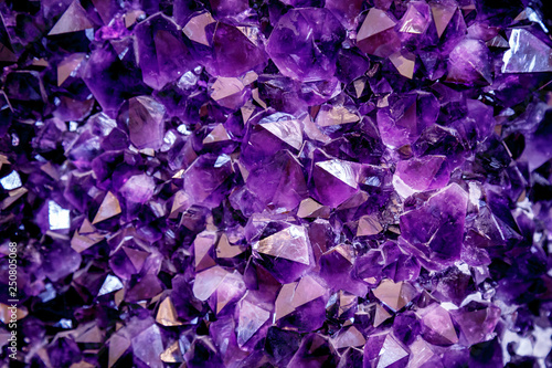 Amethyst purple crystal. Mineral crystals in the natural environment. Texture of precious and semiprecious gemstone.