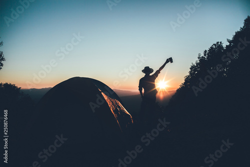Canvas Print Happy hiker man in a hat holding a coffee cup near camping tent on mountains at sunset background