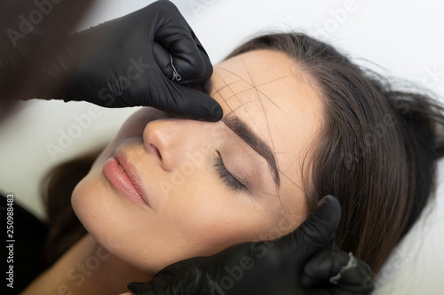 Fotografija Beautician in the saloon doing the perfect architecture of eyebrows