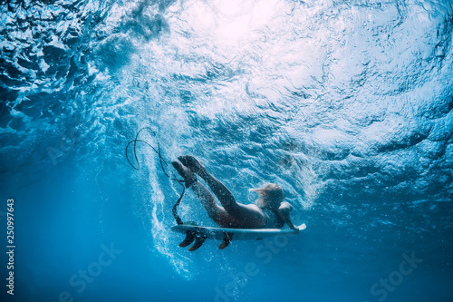 Photo Attractive surfer girl dive underwater with under wave.