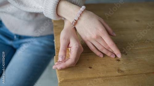 Fotografia, Obraz the girl on her arm has a bracelet made of pink stones (quartz), a bracelet made