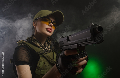 Fototapeta the girl in military special clothes posing with a gun in his hands on a dark ba