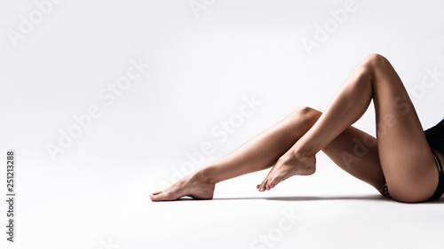 Obraz na plátně long tanned slim woman legs studio shot sit down