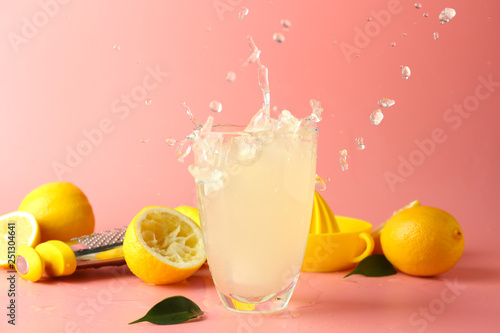 Glass of tasty cold lemonade with splashes on color background
