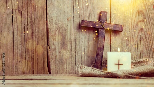 Fotografia Burning candle and cross on wooden background