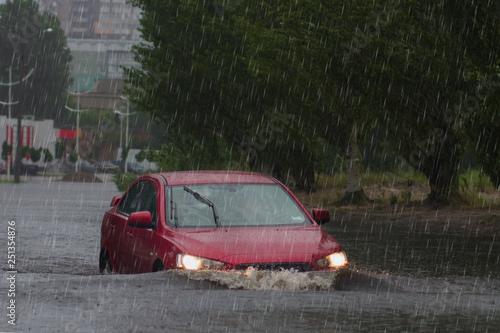 Fotografia, Obraz Red car rides in heavy rain on a flooded road