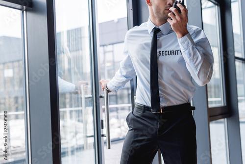 Fototapeta cropped view of handsome guard in suit talking on walkie-talkie