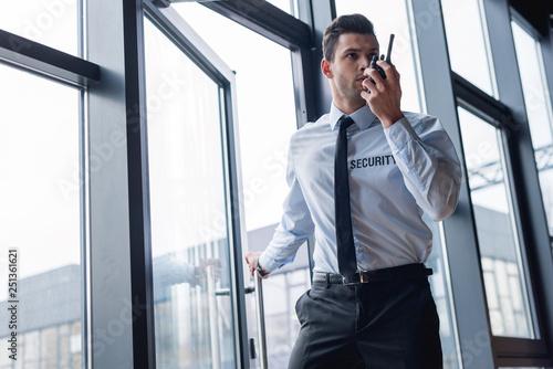 Fotografie, Obraz handsome guard in suit talking on walkie-talkie