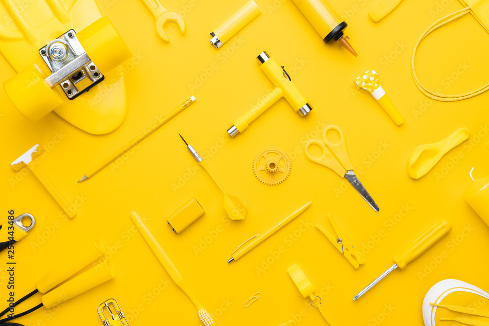 top view of random yellow objects in order on yellow background