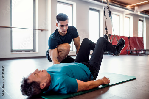 Fotografie, Tablou A senior man in gym and a personal trainer doing exercise with TRX