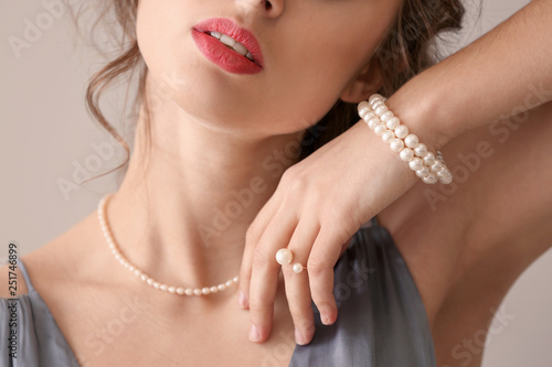 Fotografia Young woman with beautiful pearl jewelry on light background, closeup
