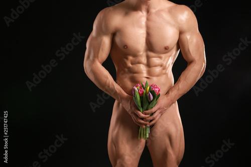 Muscular sexy bodybuilder with bouquet of flowers on dark background