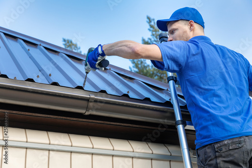 Fotografia metal roofing - roofer working on the house roof