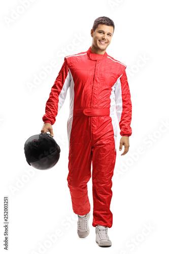 Fototapeta Male car racer holding a helmet and walking towards the camera