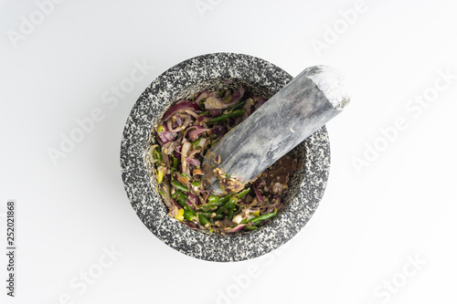Fotografia A mortar and pestle ( Lesung Batu) with mixed crushed chilies, shallots and anchovies on white background