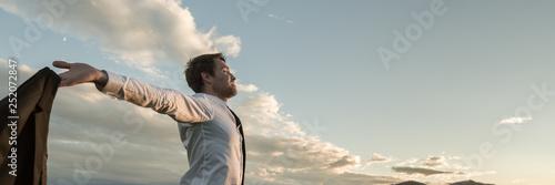Obraz na plátne Businessman embracing life standing under cloudy sky