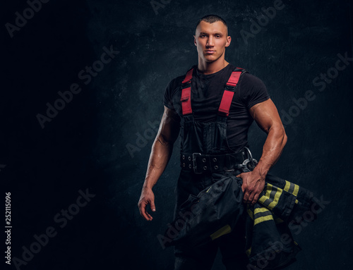 Canvas Print A brave fireman holding a jacket and looking at a camera