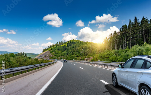 Fotografie, Obraz Car driving on highway surrounded by picturesque mountains.