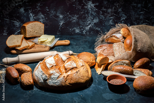 Fotografia Different kinds of bread and bread rolls on dark background