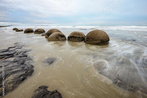 Stampa su Tela Impressive Moeraki boulders in the Pacific Ocean waves