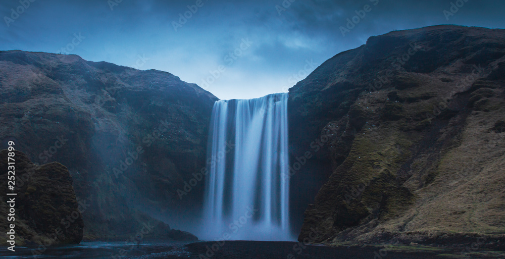 Breathtaking view of magnificent waterfall and rough cliff on beautiful cloudy day in Iceland